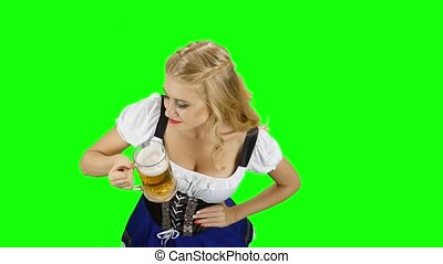 Woman in bavarian costume drinks a little of beer of glass. Green screen