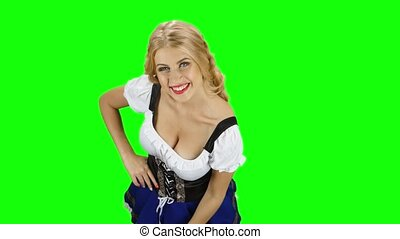 Woman in bavarian costume playing with her hair and laughs. Green screen