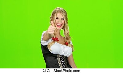 Woman in bavarian national costume laughs and shows thumb. Green screen
