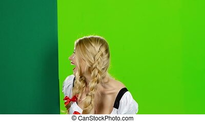 Woman in bavarian national costume waving. Green screen