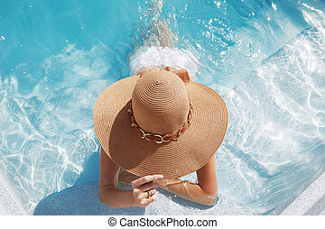 Woman in beach hat enjoying in swimming pool on Tropical Resort. Exotic Paradise. Travel, Tourism and Vacations Concept.