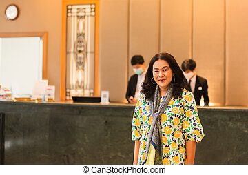 Woman in beautiful dress standing on front of hotel reception.