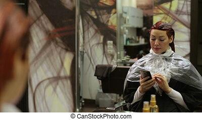 Woman in beauty salon writing sms
