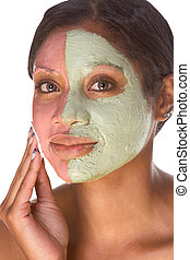 Woman with special facial mask applied on her face. The mask consist of two colors (red and green), each cover different part