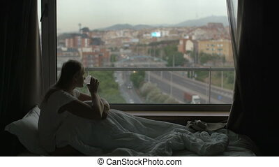Woman sitting under blanket on bed, drinking tea and looking at the city through the window. Sadness and depression