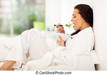 woman in bed eating fresh green salad