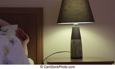 Woman in bed falling asleep turning off bedside lamp at night