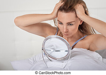 Woman in bed looking at herself in a mirror
