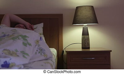 woman in bed turns off light lamp on bedside table and falls asleep