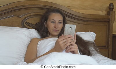 woman in bed with a phone