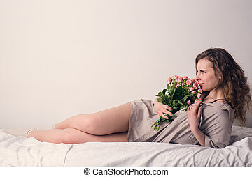 Woman in bed with bouquet