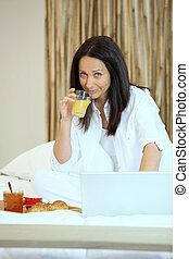 Woman in bed with breakfast and her laptop