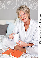 Woman in bed with coffee mug