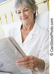 Woman in bedroom with newspaper smiling