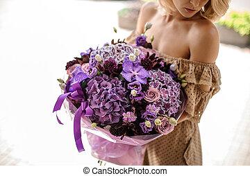 Woman in beige dress holding a big bouquet of flowers in purple tones