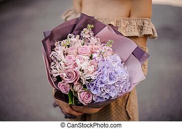 Woman in beige dress holding a romantic bouquet of flowers in purple tones