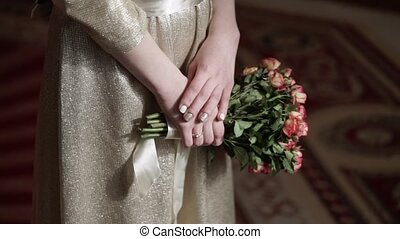 Woman in beige dress with bouquet of pink roses indoors