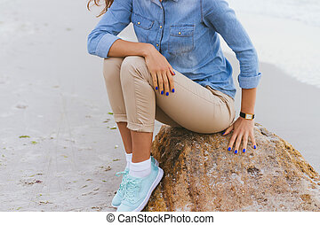 Woman in beige pants and a denim shirt and turquoise sneakers sitting on a rock by the sea. Shirt sleeves rolled up, watch on her arm, a blue manicure.