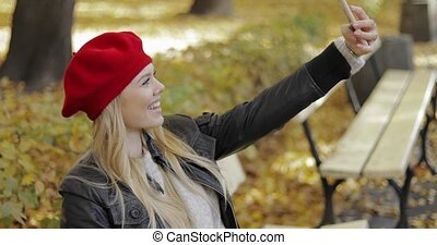 Woman in beret taking selfie in park