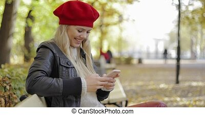 Woman in beret using smartphone in park