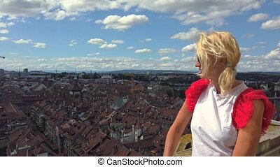 Woman tourist pointed Bern old town, capital of Switzerland, from panoramic terrace of Bell Tower Cathedral. Aerial view of cityscape of medieval city UNESCO World Heritage. Tourism in Switzerland.