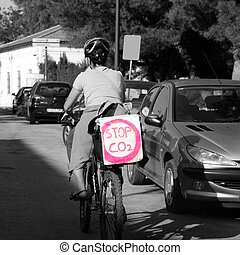 woman in bicyle with a message: stop co2