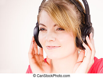 Woman in big headphones listening music