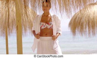 Woman in bikini and beach top under umbrella