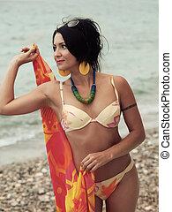 woman in bikini and pareo at sea background