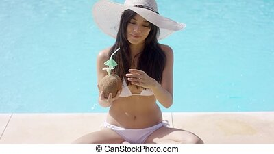 Woman in bikini and sun hat sits crossed legged