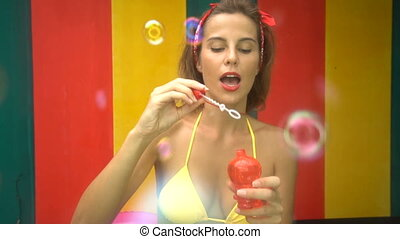 Woman in bikini doing soap bubbles