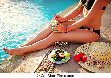 Woman in bikini drinking cocktail and eating fruits by swimming pool. All inclusive. Summer vacation