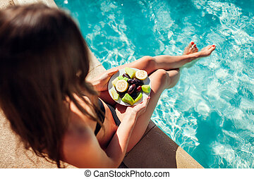 Woman in bikini eating fruits and relaxing in swimming pool. All inclusive. Summer vacation