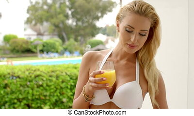 Woman in Bikini Holding Glass of Orange Juice