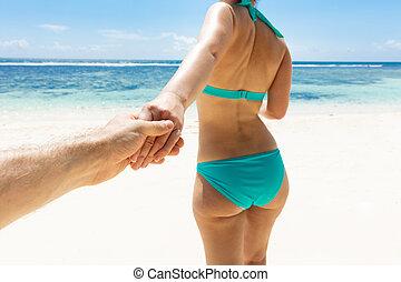 Woman In Bikini Holding Hand Of Her Boyfriend On Beach