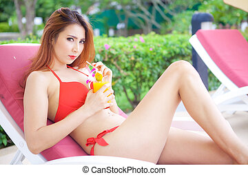 Woman in bikini lying on a deckchair - Beautiful young asian...