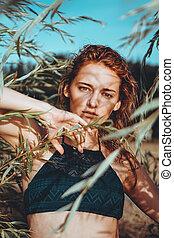Woman in bikini on a tropical beach with plants