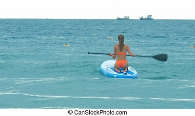 woman in bikini paddles board sitting on knees in ocean