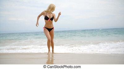 Woman in Bikini Playing in Beach Surf