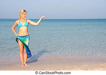Woman in bikini presenting the sea vacation
