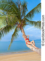 Woman in bikini reclining on palm tree trunk
