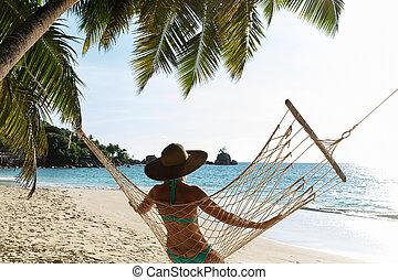 Woman In Bikini Sitting On Hammock On The Beach