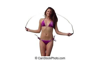 Woman in bikini skipping against a white background