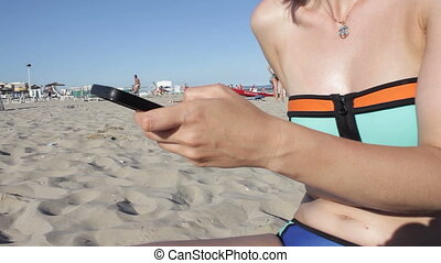 Woman in bikini sms texting using app on smart phone at the beach. Closeup of hands using smartphone outdoors. Mobile cell phone close up.