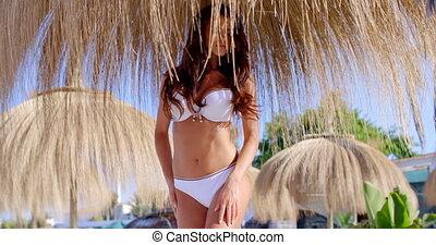 Woman in Bikini Standing Under Beach Umbrella - Brunette...