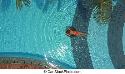 woman in bikini sunbathes on ring in hotel pool