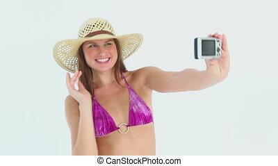 Woman in bikini taking pictures of herself