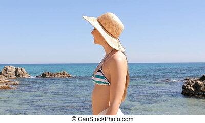 Woman in bikini walking on the beach on vacation - Side view...