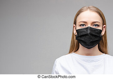 Woman in black aseptic respirator. Corona virus protection concept.
