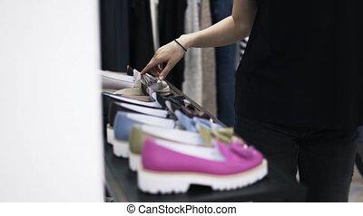 Woman in black choosing shoes in a shop